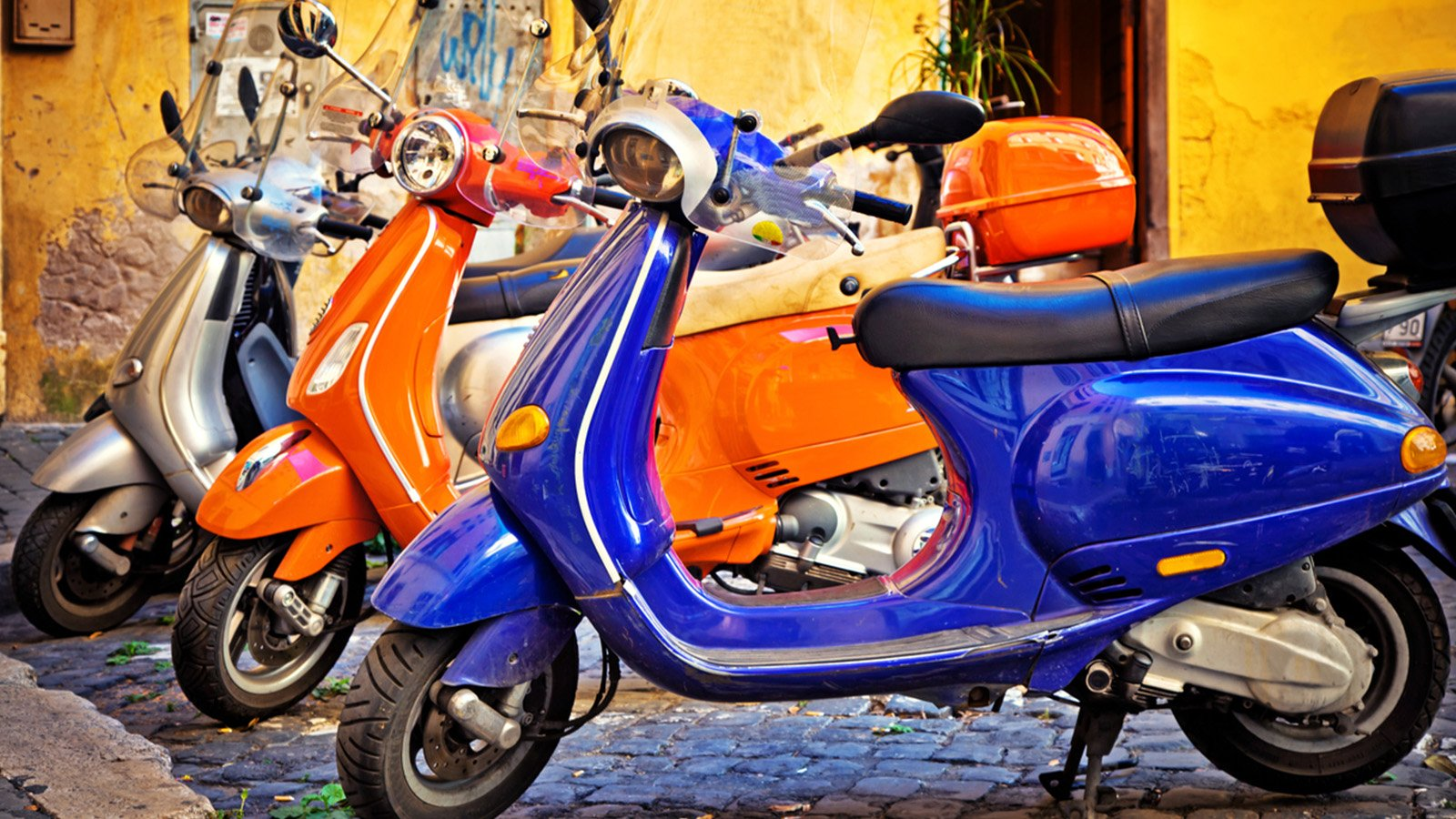Three Vespa's in blue, silver and orange in the streets of Rome