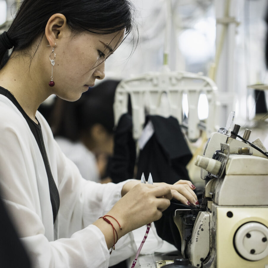 A young woman sews Masha Ma clothing in a factory just outside of Shanghai, China.
