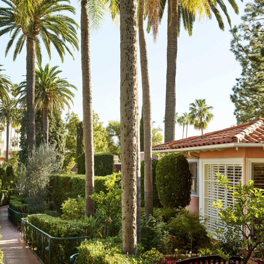 View of bungalow gardens pink building with palm trees