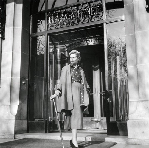 Christian Dior model strikes a pose in front of Hôtel Plaza Athénée, 1955