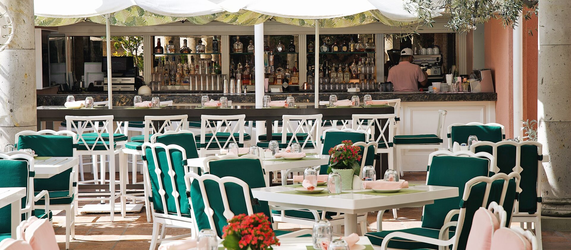 White chairs with green cushions at a bar in Beverly Hills
