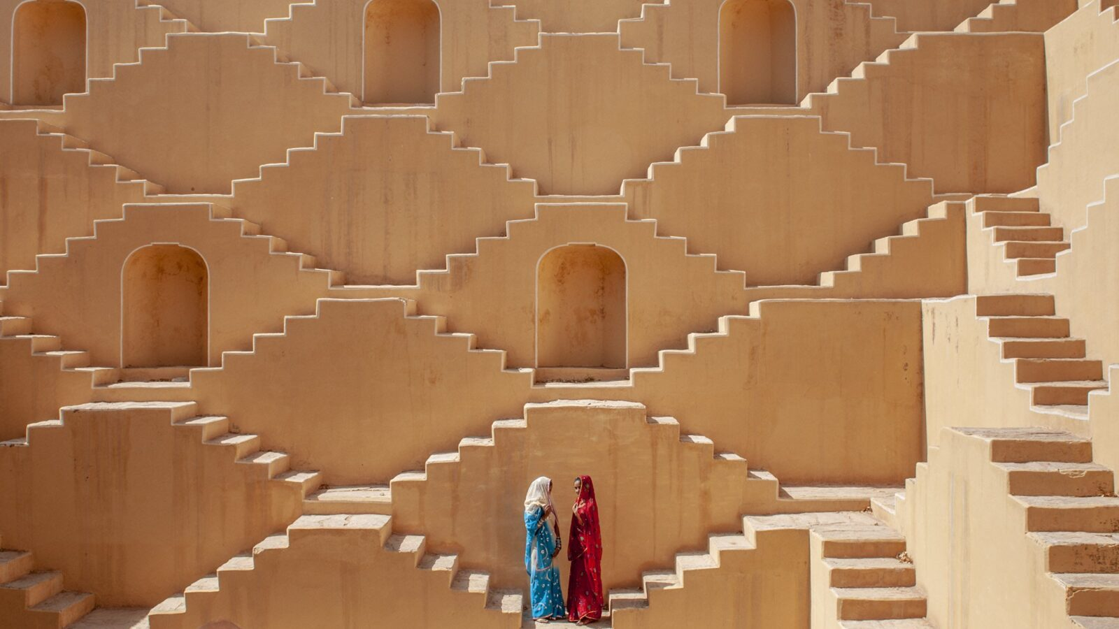 Jasmin (wearing red) and Manisha Singh (white and blue sari) pose at the Baoli at Amer, a water well in the city of Japiur in India's Rajasthan Thar desert. (Photo by Ami Vitale)