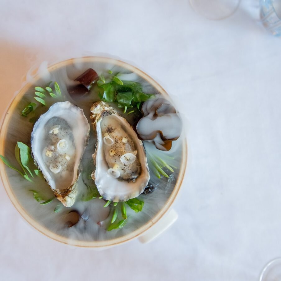 Pictures of oysters in a plate with smoke all around.