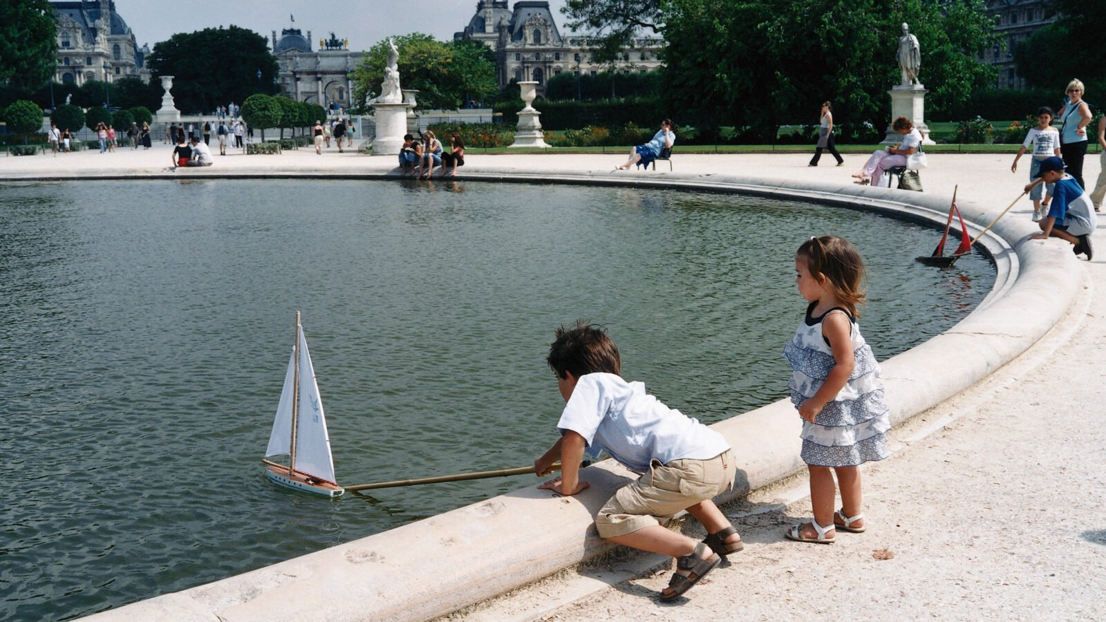 this image shows two children playing with boats on a fountain of the tuileries garden in Paris