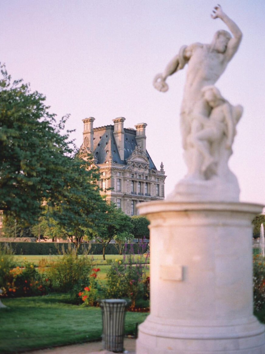 This image shows a statue and the Louvre museum from the Tuileries garden