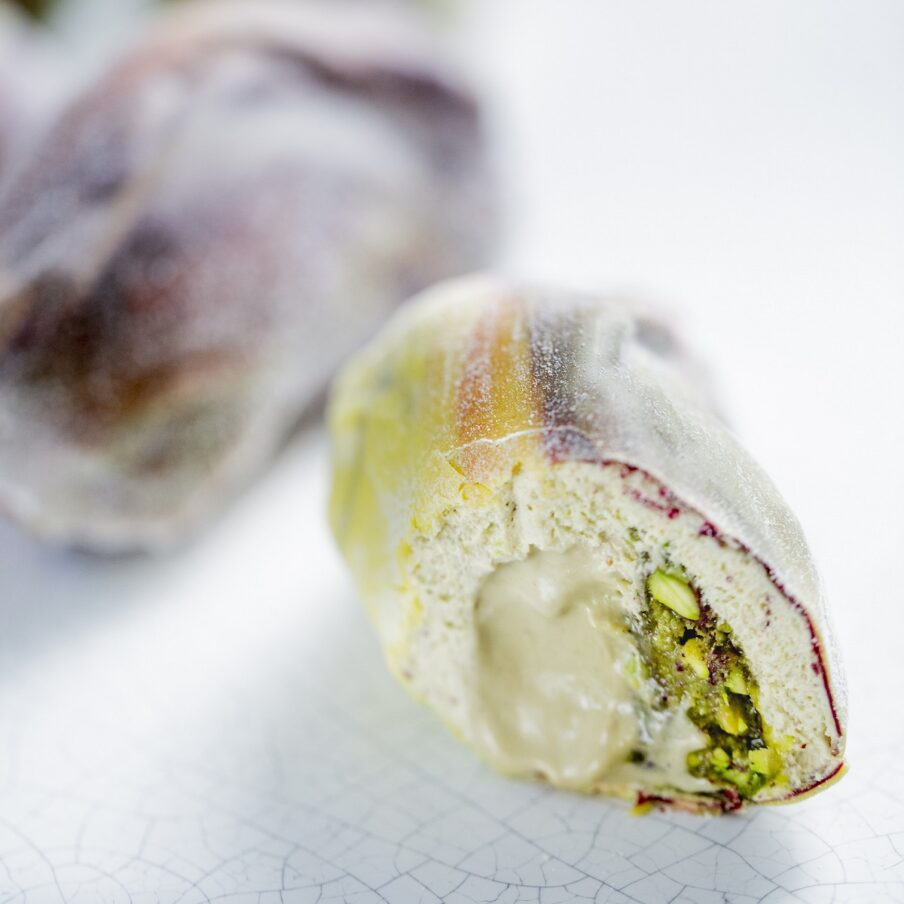 Picture of a pistachio sculpted pastry, cut in half, marble background.