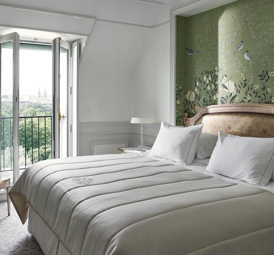 Inside a room at Le Meurice's newly restored suite with king size bed and open french doors