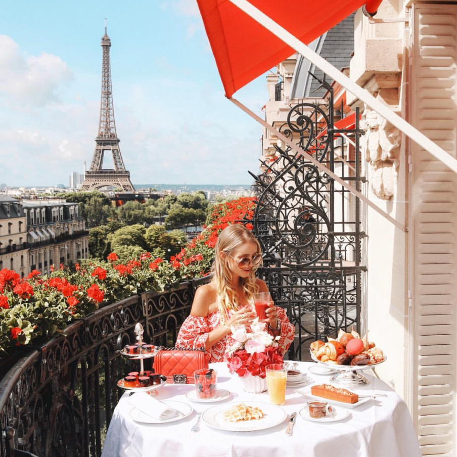 Picture of a girl having breakfast on a balcony with Eiffel tower in the back.