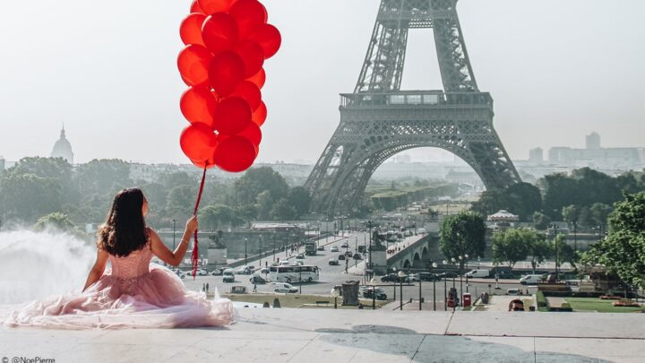 A lady holding red balloons in front of the eiffiel tower