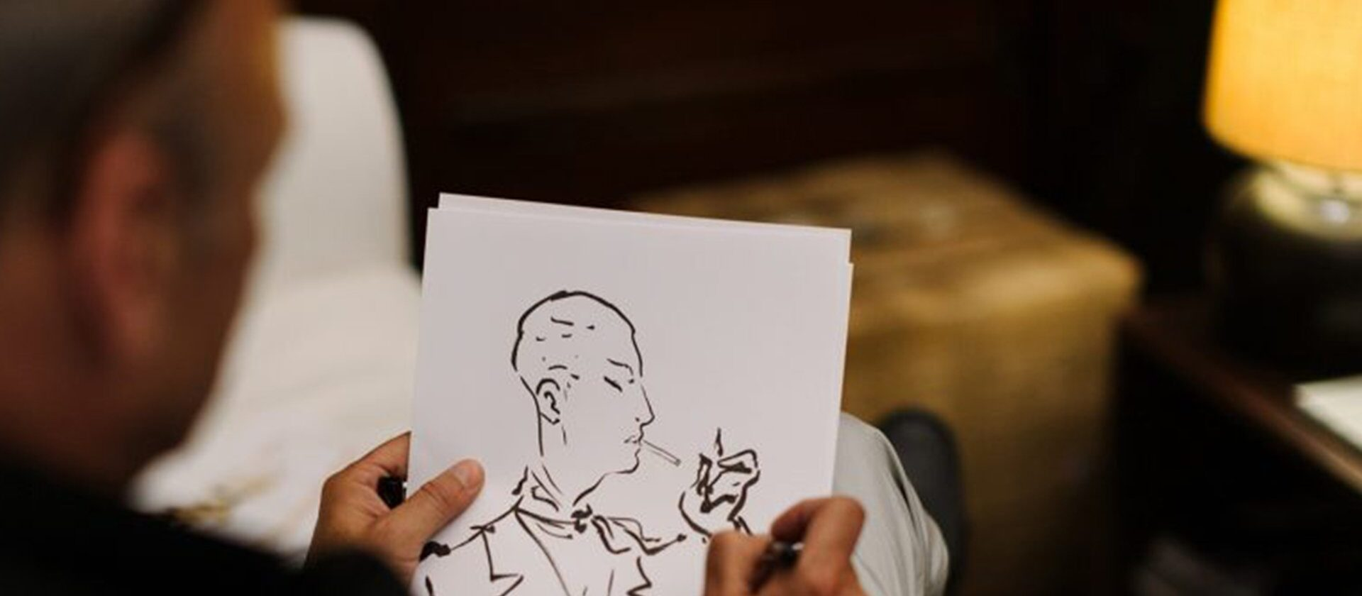 Italian Illustrator Andrea Ferolla doing a drawing of a man smoking