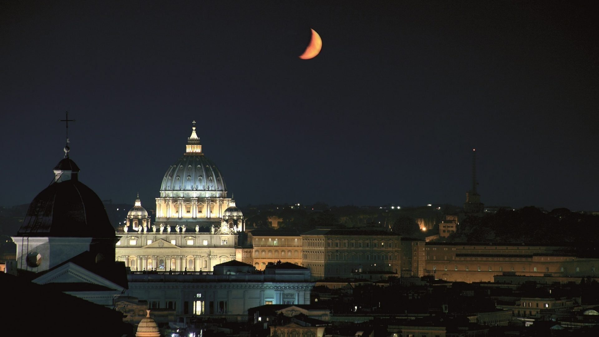 The view of Rome at night with St Peter's Basilica in the background