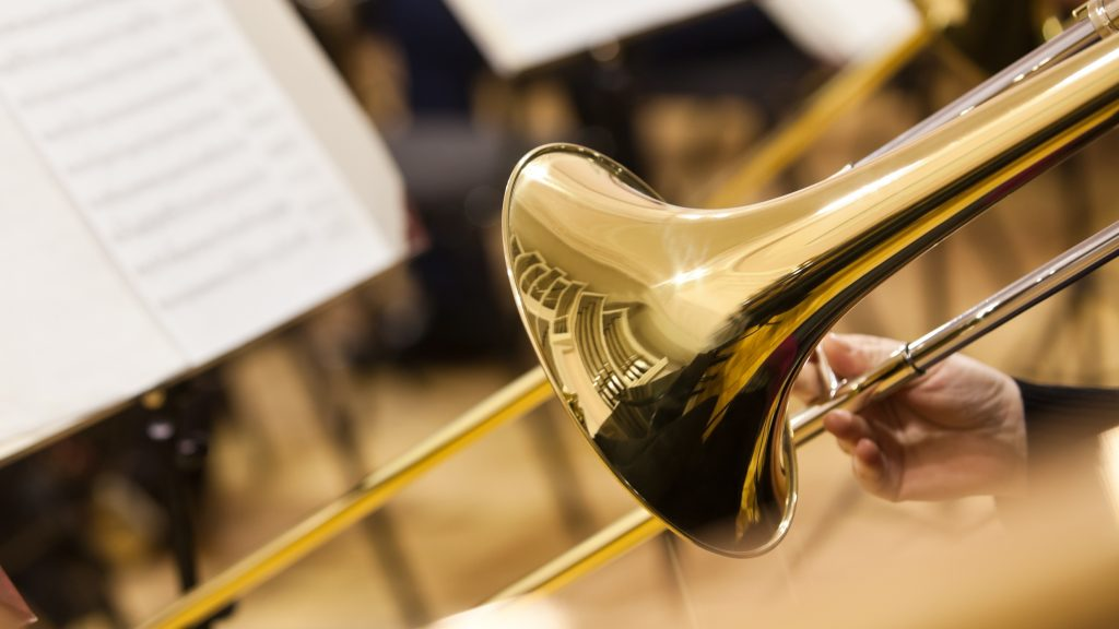 Close up of a gold trombone with sheet music in the background